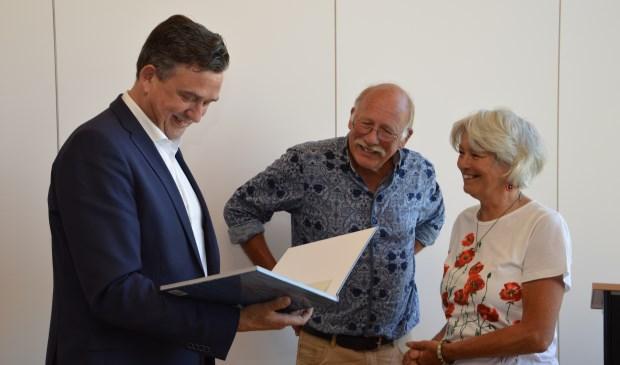 """Emile Roemer bekijkt het boek """"Texel in stukjes"""" dat hij zojuist van Adriaan en Sytske Dijksen heeft ontvangen."""