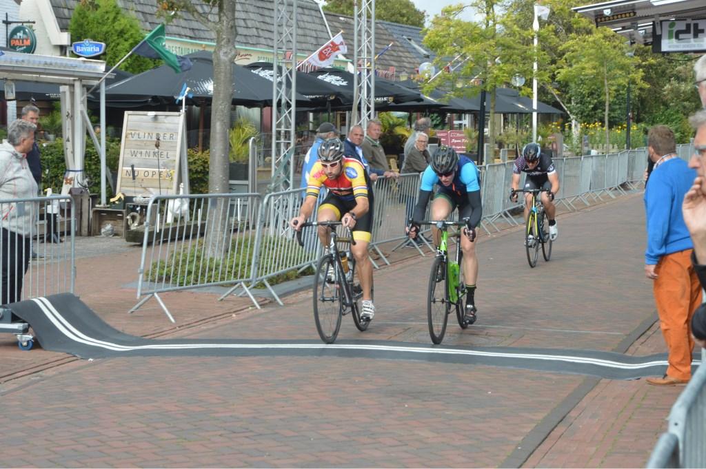 Vriend en Huijsman (rechts) naast elkaar over de finish in de één na laatste ronde. Achter hen een achterblijver.