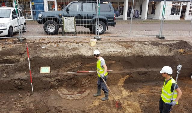 Een medewerker van Arceologie West-Friesland kijkt naar de restanten van de plaggenput.