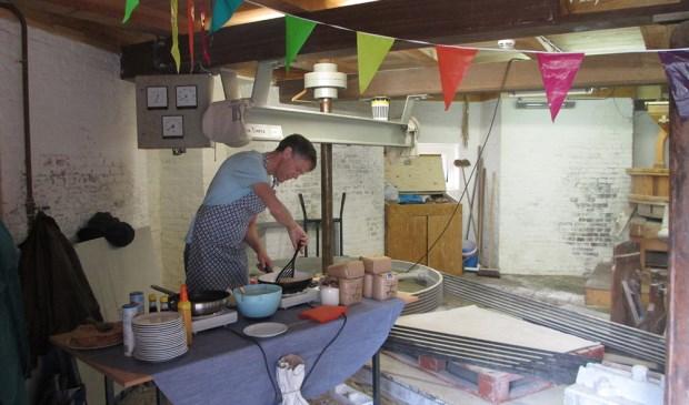 Vrijwilliger Hans Smallenbroek bakt pannenkoeken.