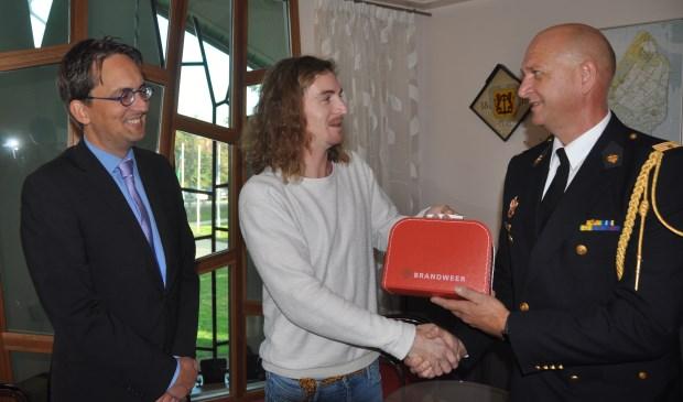 Wouter Krab krijgt de geboortekoffer van de brandweer uit handen van brandweercommandant Jelle de Boer en burgemeester Michiel Uitdehaag.