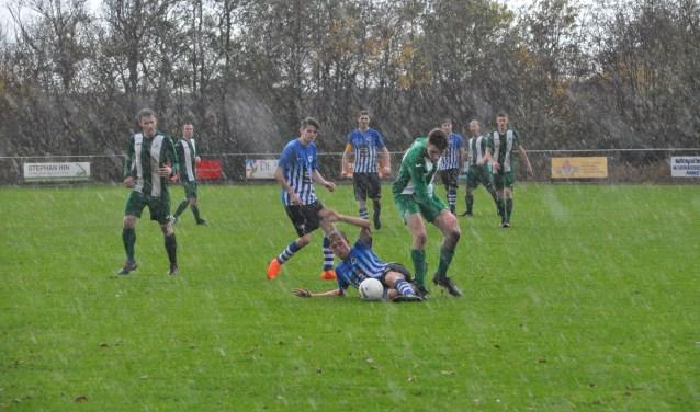 Terwijl de regen met bakken uit de hemel valt, vechten ZDH-speler Barry van der El (links) en Marijn Bakker van Oosterend een verbeten duel uit. (Foto: Willem Sangers)