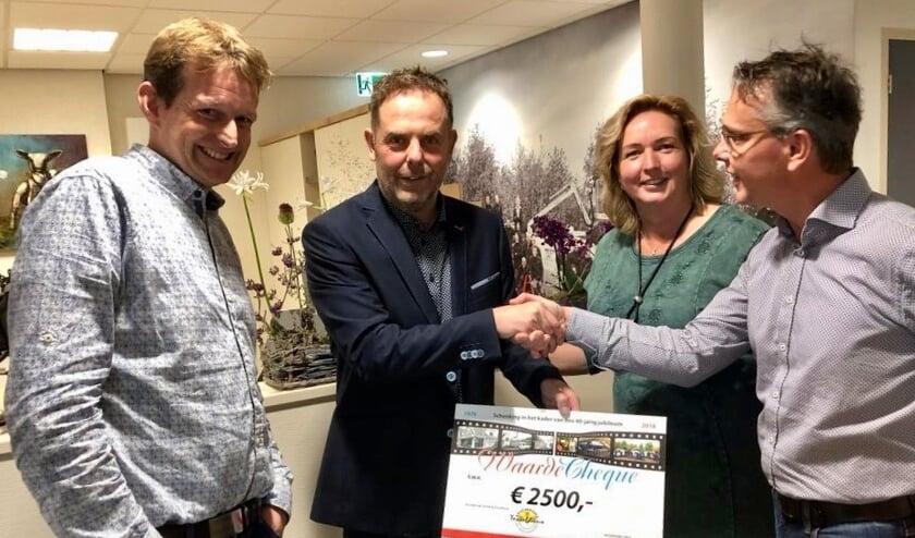 Menno en Corina Schuijl overhandigen de cheque aan Ingmar Veeger en Jan Klok van het Tesselhuus.