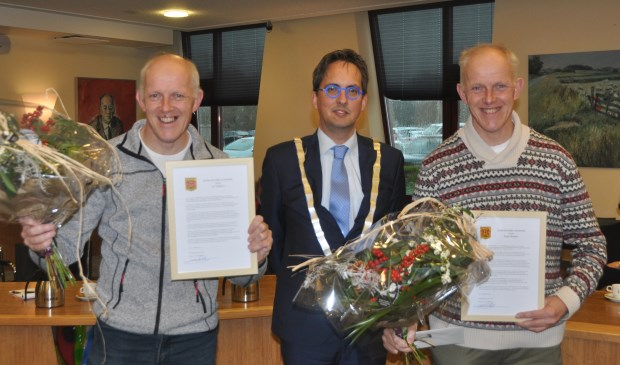 Jos (links) en Paul (rechts) met de gemeentelijke oorkonde die ze van burgemeester Michiel Uitdehaag kregen.
