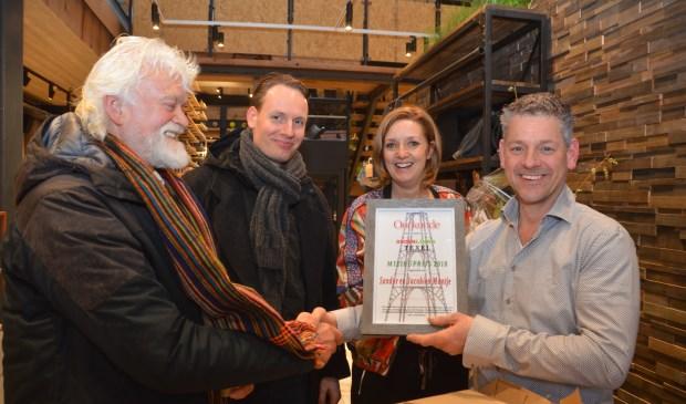 Jaap Vlaming en Sander van Knippenberg overhandigen de Groen Links Milieuprijs aan Sandor en Jacobine Mantje bij de opening van hun nieuwe winkel in De Koog.