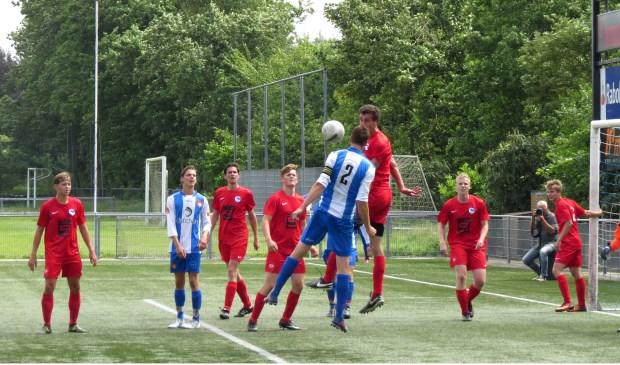 Aanvoerder Daniël Bakker kopt bij een corner de bal weg uit de doelmond.