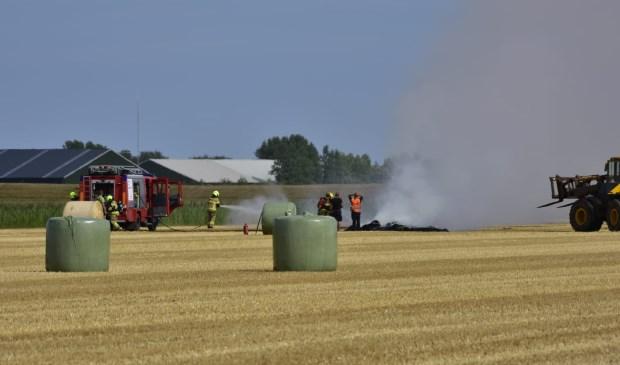 De brandweer blust de brandende hooibalen.