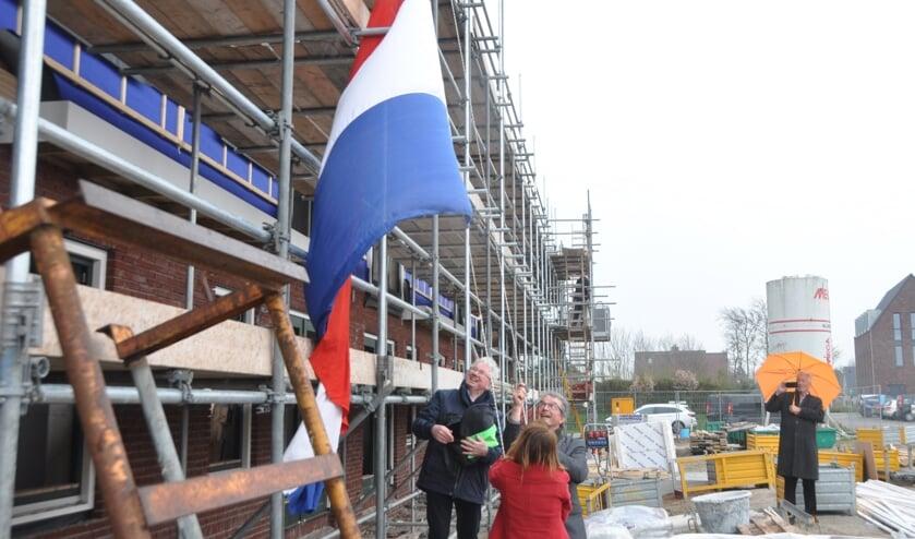 Wethouder Hennie Huisman en Jan van Andel hijsen de vlag.