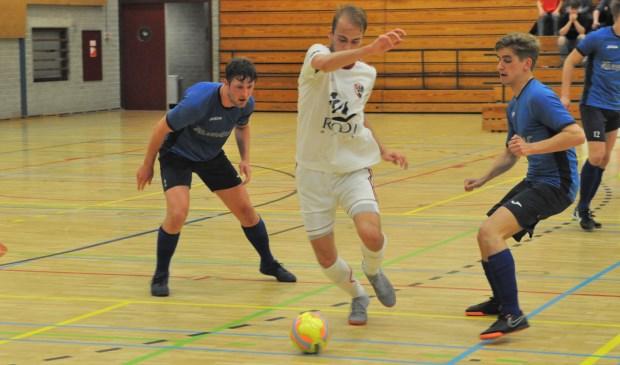 Jesper Arkenbout en Jesper List van Texel'94 Futsal en een speler van White Stones in duel om de bal.