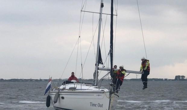 Een paar man van de KNRM in de giek van de Time Out om het schip los te krijgen van de Bollen.