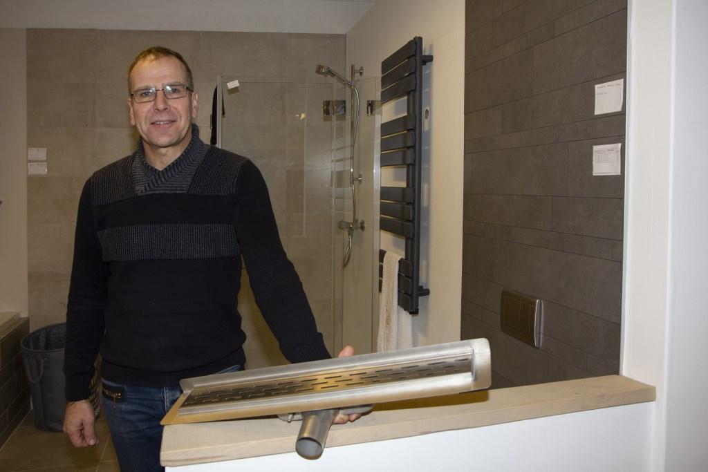 Verkoopadviseur Klaas Algra toont de drain die onder de vloer komt in een moderne badkamer. Gegarandeerd lekvrij. Foto: Actief Media © Actief Media