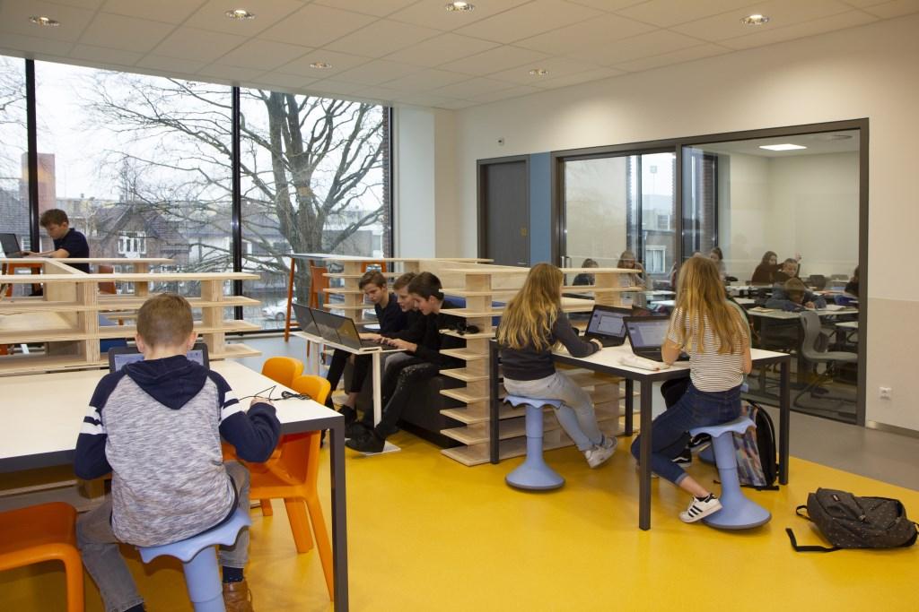 Het werkplein, met daarachter één van de vier klaslokalen waar leerlingen les hebben. Er zijn bewust veel verschillende soorten zit- en staplekken gecreëerd. Foto: Actief Media © Actief Media