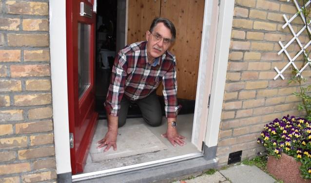 Wim de Graaf toont de vochtplek onder het vloerkleed achter de voordeur.