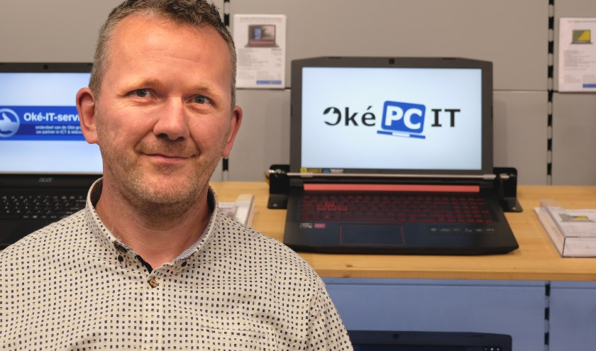 Ronald Zijlstra, met op de laptop achter hem het nieuwe logo van Oké-PC.