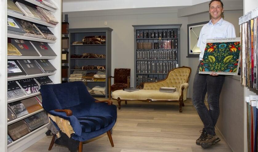 Rienk Kooistra in de vernieuwde winkel van Meubelstoffeerderij Dokkum. Er is keus uit honderden meubelstoffen. Pluchen tafelkleden vindt men hier ook nog.