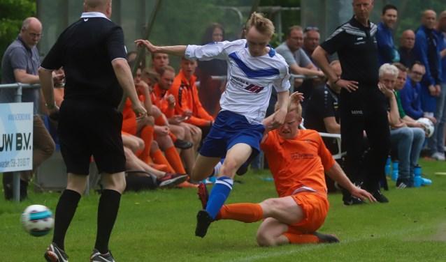 Yannick Hoekstra van Kollum (oranje tenue) probeert Jorn Geert Kramer van Rijperkerk het spelen te beletten.