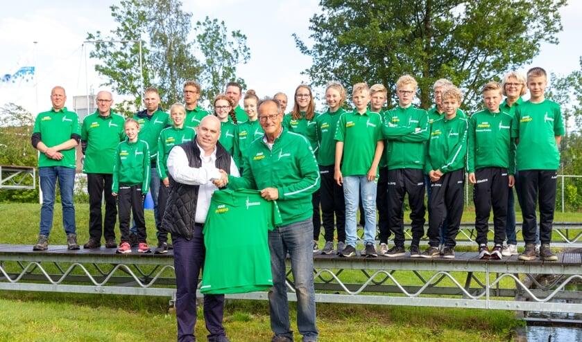 Johan Postma, bedrijfsleider van Jumbo Burgum (links voor), overhandigt het nieuwe clubshirt aan Hans Helmholt, voorzitter van Ljeppersclub Burgum. Op de schans staan leden en vrijwilligers van de club.