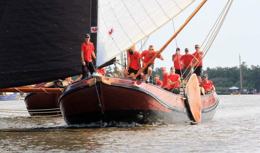Het skûtsje van Earnewâld met schipper Gerhard Pietersma aan het helmhout op weg naar de finish in de Langesleat.