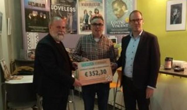 Voorzitter Harri de Vries overhandigt de cheque aan Thomas Povel en Leon Vliegen van HDKT (foto: Filmhuis Zevenaar)