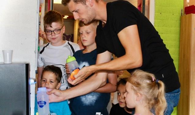David Zweekhorst tapt samen met de kinderen van BSO De Superster een flesje water.