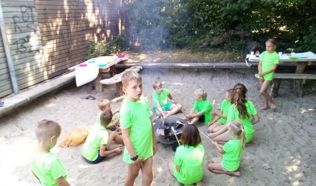 De kinderen bakken hun eigen stok-brood boven een vuurtje (foto: Doran Leijser)