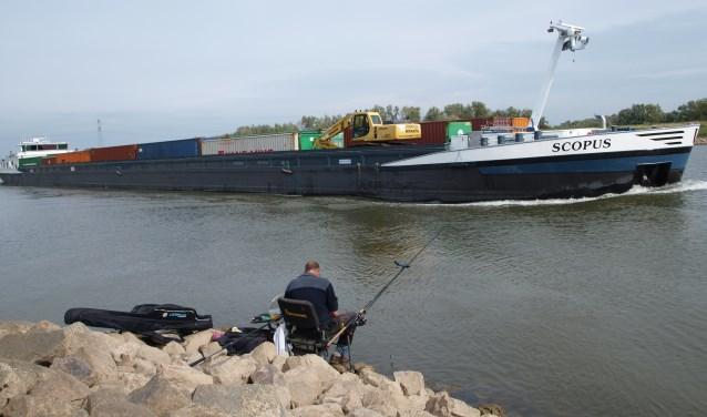 Deze foto is gemaakt op de Rijn, met een lengte van 109 meter en 35,05  breed. De visser valt hierdoor in het niets weg als zo'n groot schip passeert. (foto: Frans Willemsen)