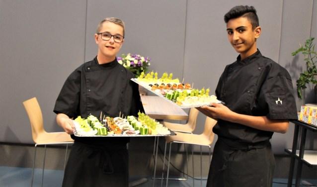 Rowdy (links) en Hani serveren trots de hapjes die ze gemaakt hebben op de eerste burenavond. (Foto: M. Kleinpenning)