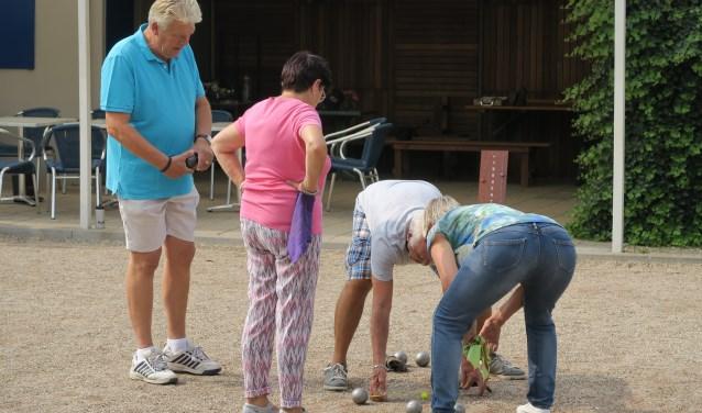 Frans Smit gaat nauwkeurig meten welke boule 'ligt'. (foto: Jeu de boulesclub Lingewaard)