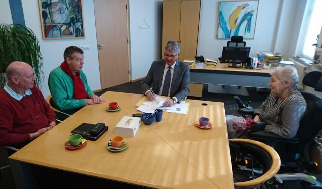 Het tekenen van de akte. Van links naar rechts Rob van Hummel, Adri van Zundert, notaris Swetselaar en Ans Venhorst. (foto: E. Janssen)