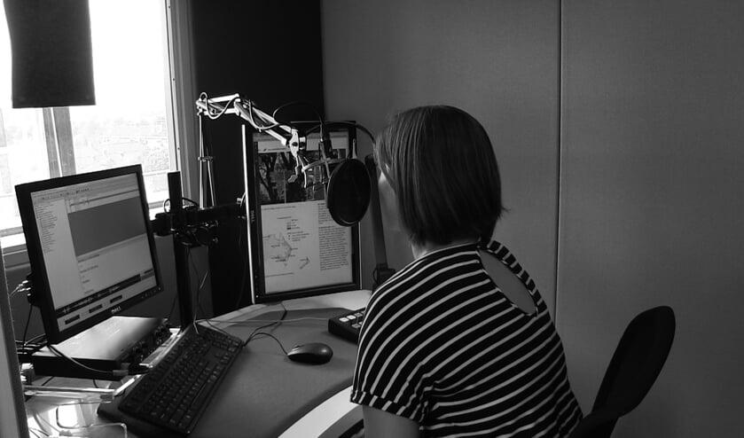 Een vrouw zit in een opnamestudio en leest vanaf een scherm een boek voor (foto: Iris Knuit)