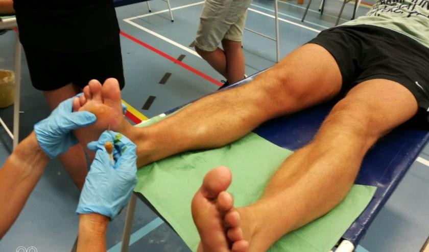 Een Rode Kruisvrijwilliger behandelt de blaar van een Vierdaagseloper. (foto: Eric Versteeg/(Rode Kruis)